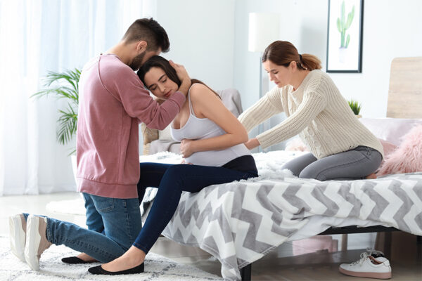 Laboring woman sitting on bed, supported by partner and doula